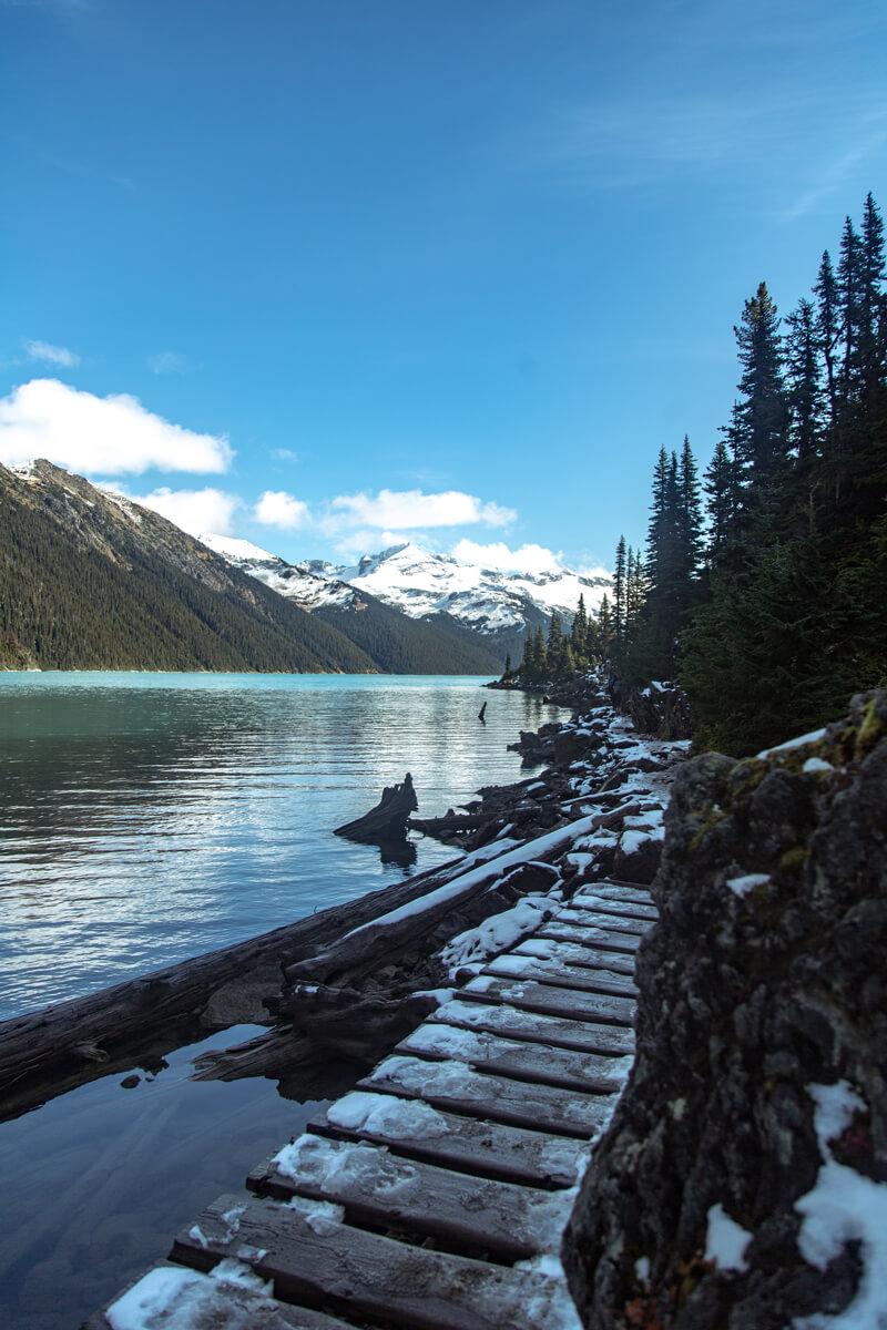 Un sentier enneigé au bord du lac Garibaldi avec les montagnes impressionnantes à l'arrière-plan