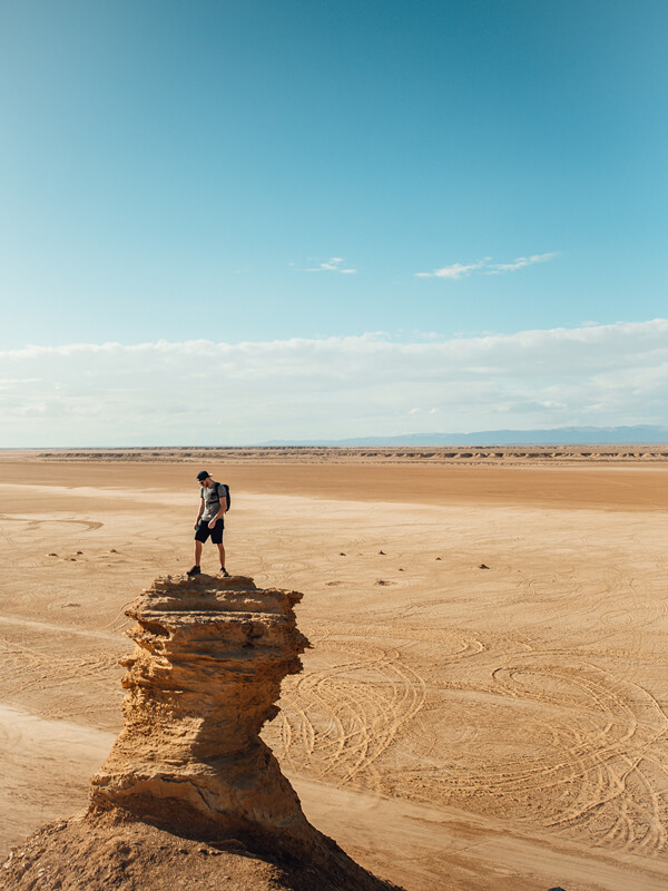 Benoit Chamberland on the top of a rock formation in the desert