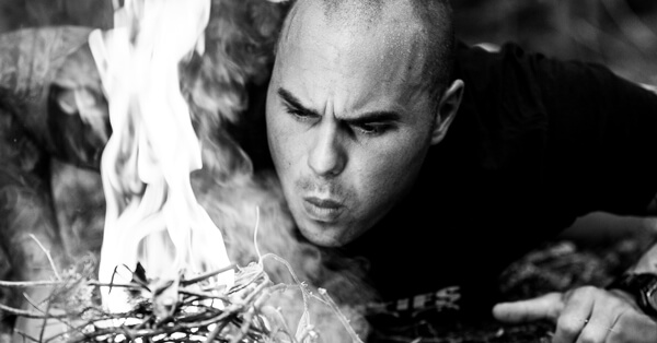 Keven Martel lighting up a fire during his survival training