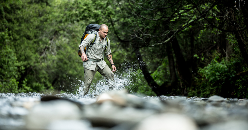 Keven Martel on an expedition, crossing a river with his LOWA boots