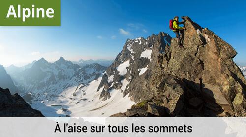 Un athlète de la LOWA qui atteint le sommet d'une crête montagneuse par une belle journée ensoleillée.