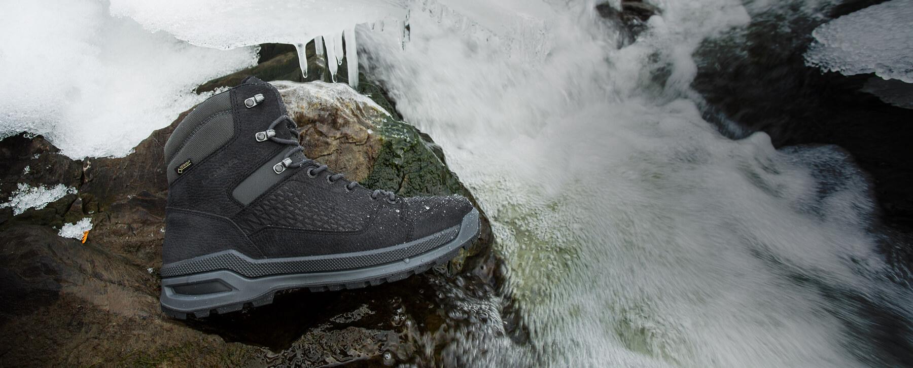 Une botte d'hiver LOWA Locarno ICE GTX MID MID sur un rocher près d'une chute d'eau pendant l'hiver.